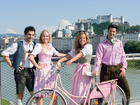In Lederhosen and Dirndl on the Makartsteg with the view to the fortress | © Tourismus Salzburg GmbH